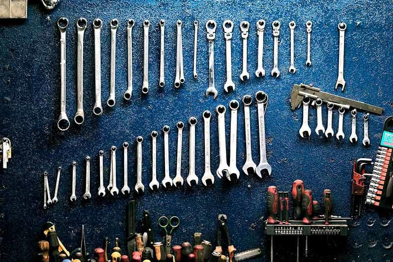 Työkaluja roikkumassa seinällä.