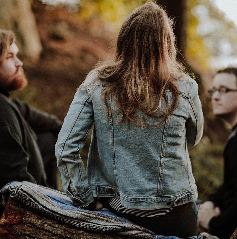 Kaksi miestä ja yksi nainen istumassa metsässä ja keskustelemassa