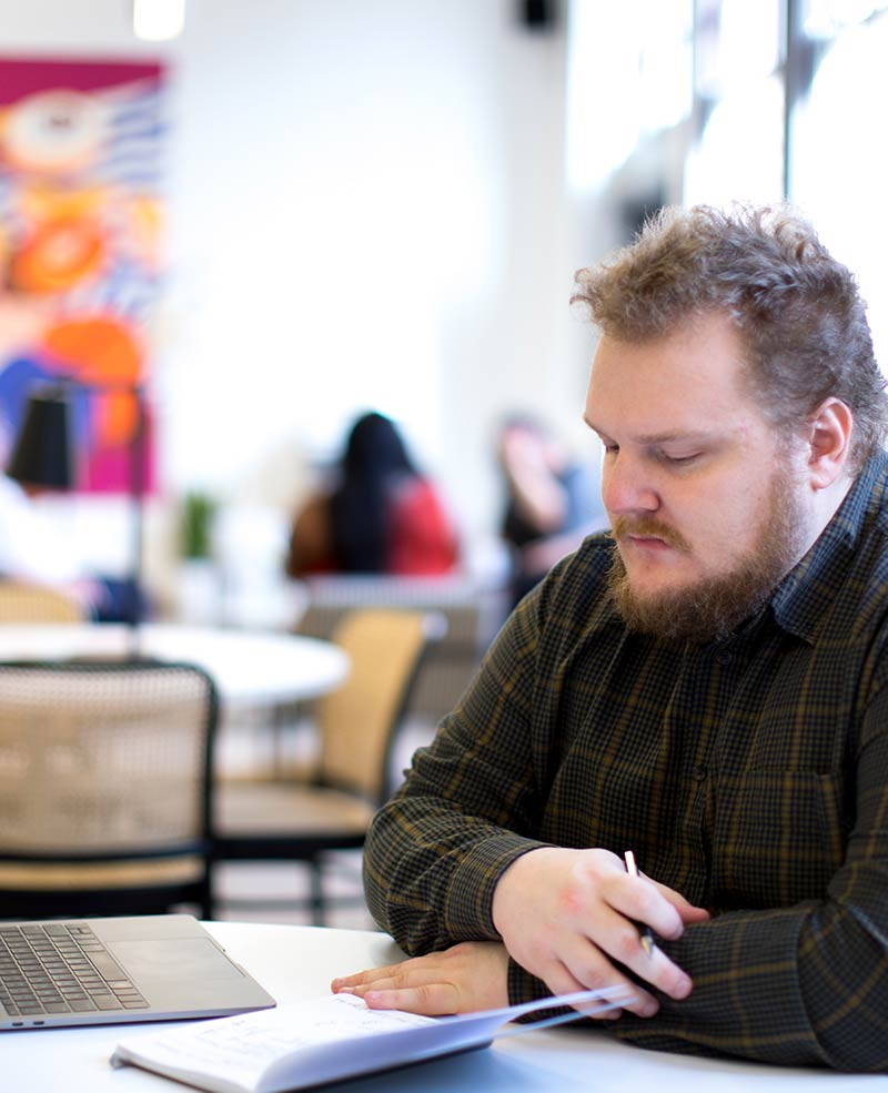 Mies istuu pöydän ääressä, kädessä kynä ja edessä vihko.