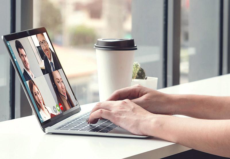 Ihmisen kädet tietokoneen näppäimillä, tietokoneen näytöllä ihmisiä videotapaamisessa.